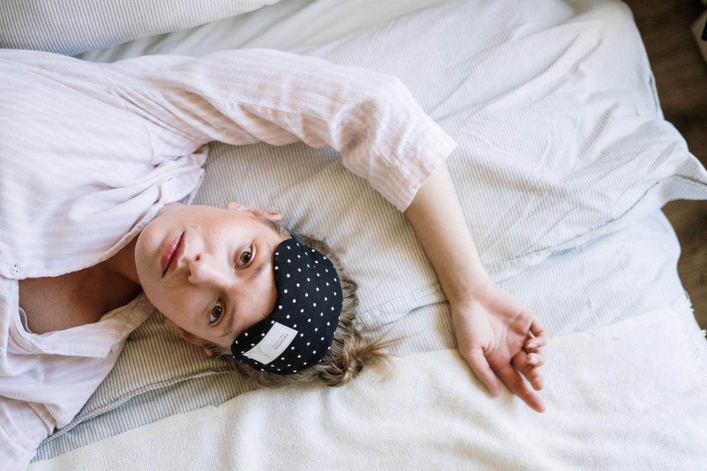 Billede af kvinde der ligger i sengen og har problemer med at falde i søvn.