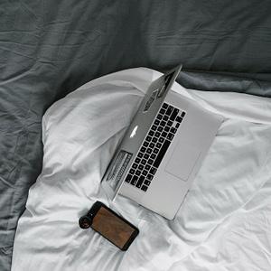 Billede af Laptop og mobiltelefon i en seng. Det kan påvirke din søvn negativt.