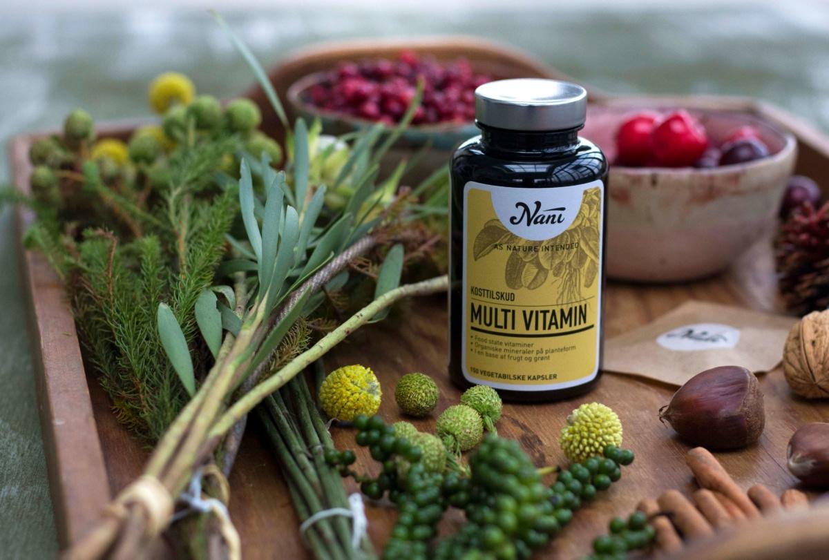 Multivitamin på bakke med urter og bær
